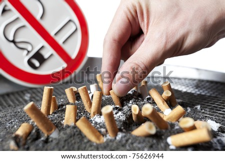 Close up of human hand with cigarette butts stuck in ash with no smoking sign in background.
