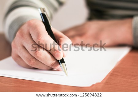 Close up of human hand with pen - stock photo