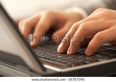 Close-up of human hands pushing keys of laptop or computer