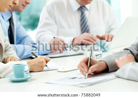 Close-up of human hands with pens over financial documents - stock photo