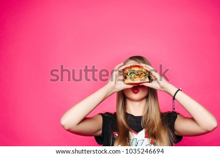 Close up of hungry girl with opened mouth, holding and eating big hamburger. Pretty woman with curly hairstyle and red lips eating tasty cheeseburger with tomato and meal. Concept of fast food.