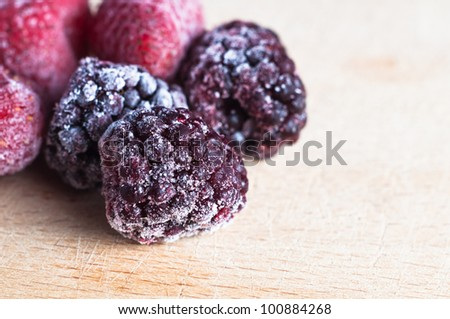 Close up of ice frosted frozen berry fruits, on an old, scratched wooden chopping board.  Landscape orientation.