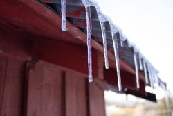 close-up of icicles falling from the metal roof of a wooden barn