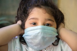 Close up of Indian baby girl wearing the mask for protect from virus and air pollution. Prevention by mask to reduce spread of the coronavirus covid-19 outbreak from human to human transmission.