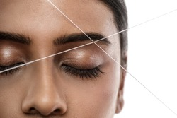 Close-up of Indian woman face with a thread. Eyebrow threading - epilation procedure for brow shape correction