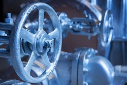 Close-up of industrial gate valve with focus on stem and nut of the hand wheel