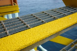 Close up of industry steel staircase with yellow anti slip plate on the tread.