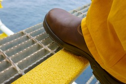 Close up of industry steel staircase with yellow anti slip plate with safety shoe step on the tread.