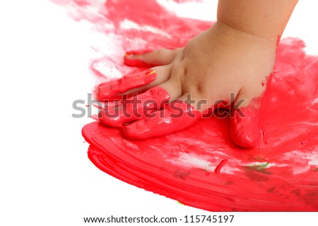 Close up of infant hand painting red mosaic.Isolated on white.