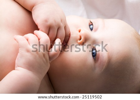 Close-up of innocent baby keeping his fingers in mouth