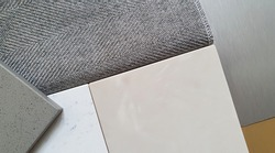 close up of interior mood and tone board showing combination of interior material containing artificial stone ,grey textile fabric for drapery ,gold and silver metallic laminated samples.