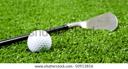 Close up of Iron golf club on green grass(artificial turf) at low angle