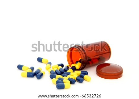 close up of isolated capsules spilling out from small bottle - stock photo