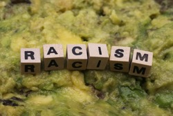 Close up of isolated word racism spelled by wooden letters on disgusting green slimy stodge (focus on word center)