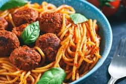 Close-up of Italian pasta with tomato sauce and meatballs in blue plate.