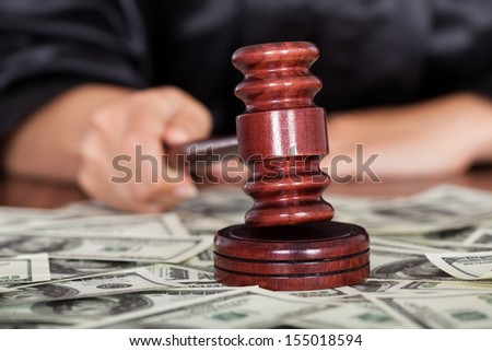 Close-up Of Judge Striking The Gavel Surrounded By Banknote