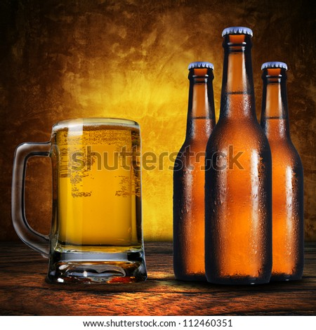 Close up of jug of beer and three beer bottles. Cold refreshment