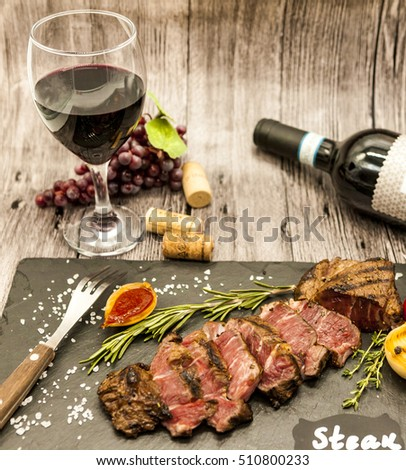 Close-up of juicy beef steak striplon with wine bottle, glass, grape and cork #510800233