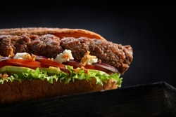 close up of kebab sandwich on black wooden background