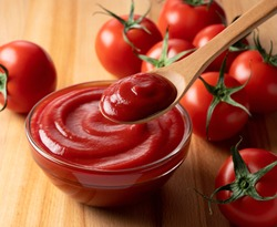 Close up of ketchup and tomatoes placed on a wooden background. Scoop ketchup with a spoon.