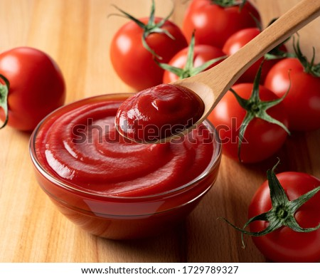Close up of ketchup and tomatoes placed on a wooden background. Scoop ketchup with a spoon. Foto d'archivio ©