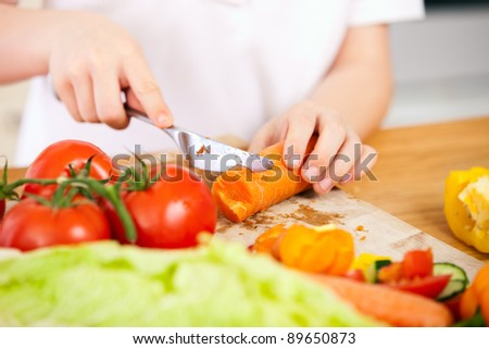 Close up of kid cutting vegetables for salad - stock photo