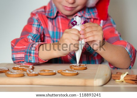 Close up of kid decorating the gingerbread cookies, Merry Christmas