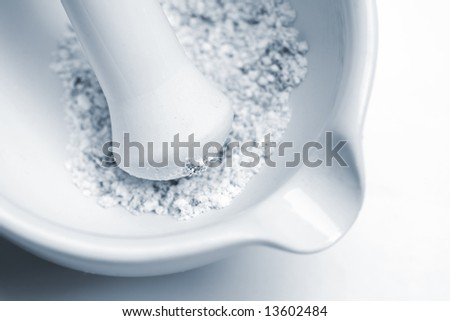 close-up of laboratory pestle in mortar with ground material, blue toned