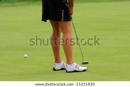 Close up of lady golfer putting