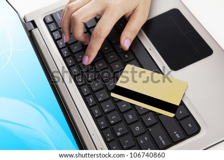 Close up of laptop computer with a credit card and a hand - payment concept