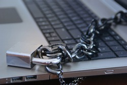 Close-up of laptop with a chain over it