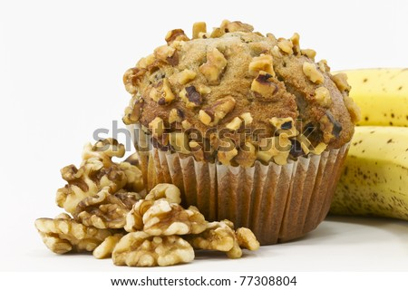 Close up of large, banana and nut muffin surrounded by shelled walnuts and ripe bananas