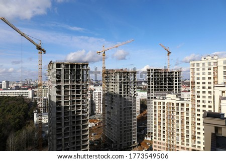 Close-up of large construction site including several cranes working on building complex. Clear blue sky with clouds. Modern industrial project and renovation concept