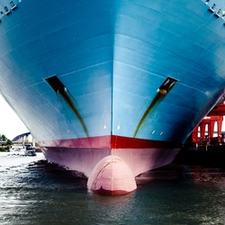 Close up of large container ship's bow from sea level in dock, plimsoll line visible