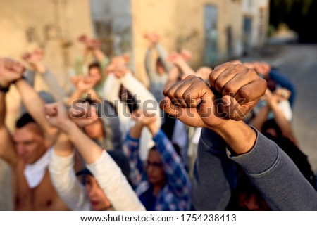 Close-up of large group of protesters with clenched fists above their heads on public demonstrations.