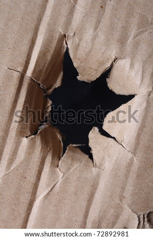 close-up of large hole in the brown paper (cardboard)