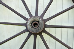 close up of large wooden cartwheel .  Round wheel with wood spokes and metal centre outside against fence panels