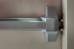 Close-up of latch and door handle of emergency exit. Push bar and rail for panic exit. Open one way door, Steel of handle for the door fire exit, Panic fire exit devices, Selective focus.