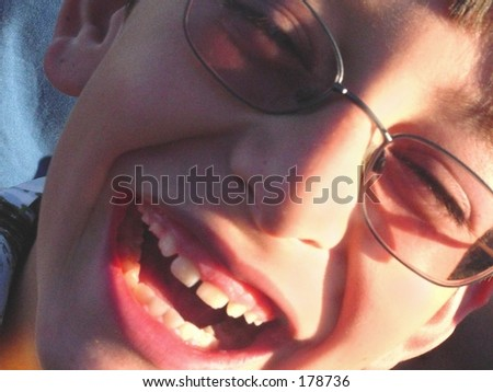Close up of laughing boy in glasses