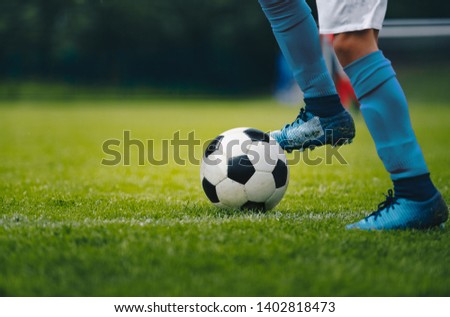 Photo of  Close up of legs and feet of football player in blue socks and shoes running and dribbling with the ball. Soccer player running after the ball. Sports venue in the background