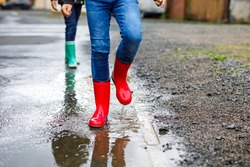 Close-up of legs of two kids boys wearing red and green rain boots and walking during sleet and rain on rainy cloudy day. Children jumping into puddle. Having fun outdoors, healthy children activity