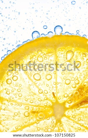 close-up of lemon slice in clear water with bubbles