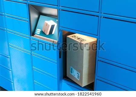 Close up Of Light Blue Self-Service Post Terminal Machine With Touchscreen Monitor and One Open Locker With Parcel Inside. Parcel In Cardboard Package. 3d rendering.
