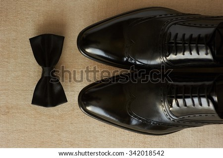 close-up of lightened with natural light men\'s shoes and bow tie. Shoes and bow tie lying on the wooden floor. They are black