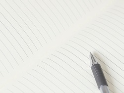 Close up of lined paper in white blank notebook with silver-gray pen.