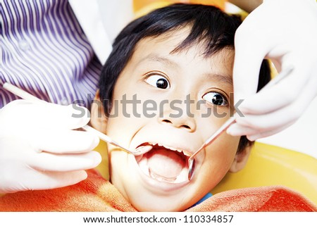 Close-up of little boy opening his mouth wide during inspection of oral cavity by dentist