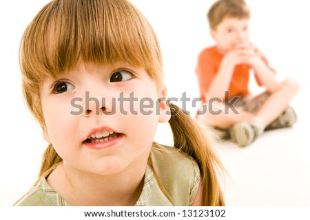 Close-up of little curious girl looking slightly aside on the background of sitting boy