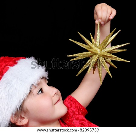 close-up of little girl in santa hat holding up golden christmas star. isolated on black