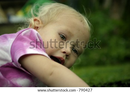 close up of little girl laying on the grass playing in soil