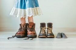Close up of little girl putting on fathers hiking shoes. Three pairs of shoes for family indoor.